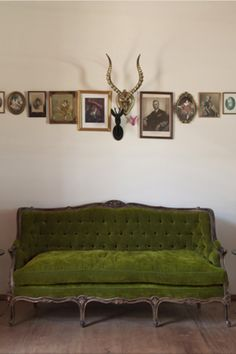mouth dropped when I saw this picture...green velvet couch from an era gone by, animal head perched with old photos line wall looks like a scene from an old saloon joint... http//desiretoinspire.net