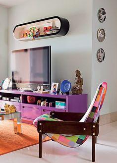 Nesta sala, tudo vibra: do móvel de TV roxo ao tapete laranja. Os três pratos, apesar de modernos, dão o tom de casa de avó. Ambiente decorado pela arquiteta Andrea Murao