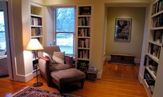 """The downstairs hall was so large that, by adding bookshelves in one corner, Chapin transformed it into a little library — making it """"a place to be"""" rather than a place """"for going through,"""" as he puts it. The bookshelves appear to be built into the wall cavities but they are not. Rather, Chapin built out from the interior walls to add a new layer, including shelves, to the interior."""
