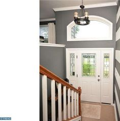 Traditional Entryway with Chandelier, Crown molding, Glass panel door, Arched window, High ceiling, Carpet