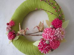 12 inch wreath wrapped in grass green yarn, decorated with handmade fabric origami cranes, pink felt flowers, berries and floral stems.