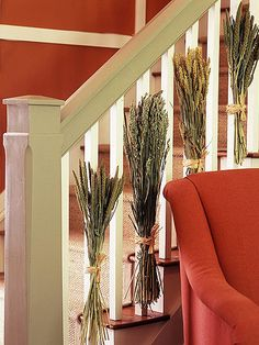 Ornamental grasses dress up a plain staircase for fall -- the dried variety is available at crafts stores and fresh grasses can be purchased at some floral shops. Simply bundle bunches of the grasses together, secure with a rubber band and tie to every other baluster on your staircase with raffia.