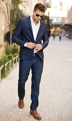 + Ideas for Cool Mens Summer Wedding Attire To Try This Season walking man dressed in a dark blue suit, with white shirt, and brown brogue shoes, wearing sunglasses and a wrist watch Outfit Hombre Formal, Formal Men Outfit, Mode Masculine, Dressy Casual Attire, Style Casual, Casual Chic, Summer Wedding Attire, Costume Gris, Dark Blue Suit
