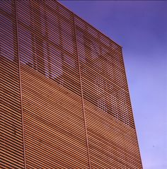 The music theatre in Albertslund, Denmark. The tower is closed by a sheath of cedarwood panels overlapped to give the tower a crisp and clean-cut external expression. By Henning Larsen Architects in 1996.