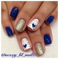 Very pretty blue, white, and gold nails with gold stripes and blue hearts.