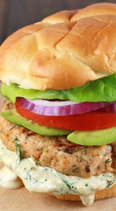 Salmon Burgers with Lemon Dill Sauce Salmon burgers with homemade lemon dill sauce takes the seafood sandwich to the next level. Healthy protein grilled to perfection and topped with lettuce, tomato, onions, and avocado. Salmon Burger Sauce, Dill Sauce For Salmon, Lemon Dill Sauce, Salmon Burger Recipes, Sauce For Salmon Patties, Canned Salmon Recipes, Lemon Salmon, Fish Recipes, Seafood Recipes