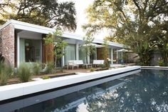 To revive the original architects' vision, studioWTA restored a four-foot roof overhang above a wall of La Cantina sliders. The shade helps limit solar gain, while a pool by Evans + Lighter Landscape Architecture provides respite on sweltering summer days. Photo 7 of Emerald Street Residence modern home