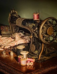 Antique sewing machine - love the little cloth cuff on the neck to hold pins.