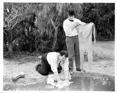 Oliver Hardy and Stan Laurel cleaning their clothes in pond in a scene from the short 'One Good Turn' 1931
