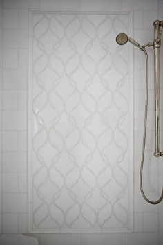 A walk in shower is clad in white translucent tiles accented with white and gray marble tiles, New Ravenna Sophie Tiles.