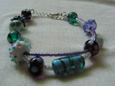 Rachel's circus bracelet - clear green, lavender, purple and teal Italian glass with white, light blue and green opaque glass - lampwork beads made by Glass in Pocket - strung with purple and white opal seed beads