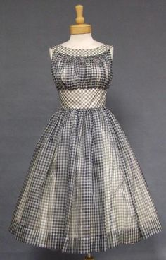 A charming 1950's cocktail dress in navy and white gingham organdy. Sleeveless, fitted bodice with gathered bustline. Dress has a full skirt (shown here with an additional crinoline... not included). Dress is fully lined in ivory acetate. Rear metal zipper