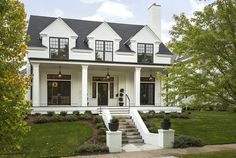 White house with black shutters exterior transitional with porch lighting dormer windows