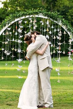 Brides.com: . A classic greenery ceremony arch goes whimsical with dozens of hanging paper cranes.