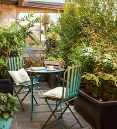 Small terrace with tiles, metal garden table and chairs in green water pickling and flower beds with plants Outdoor Spaces, Outdoor Living, Outdoor Decor, Porches, Casa Patio, Balcony Table And Chairs, Terrace Design, House With Porch, Terrace Garden