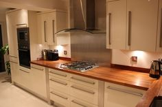 Cream Gloss Kitchen, Stainless Steel Splashback and Walnut Worktops Cream And Wood Kitchen, Cream Gloss Kitchen, Open Plan Kitchen, New Kitchen, Kitchen Wood, Kitchen Interior, Kitchen Decor, Kitchen Ideas, Kitchen Worktop