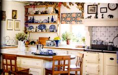 English kitchen. Notice the Aga. In historic cottages the Aga will be seated where the kitchen fireplace once was centuries ago. This is why there is usually a mantle over the cooker (range).
