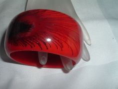 VINTAGE WIDE RED CELLULOID AND PEACOCK FEATHER BANGLE BRACELET