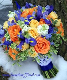 Orange, yellow, blue, and white bridal bouquet featuring roses, iris, and stock. Designed by Something Floral / Something Spectacular, Warren, MI. Photo: Urban Fire Studio.