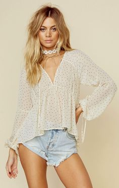 The Truffles Blouse by For Love and Lemons was made for a classic feminine look on a polka dot print that can be easily paired with anything in your closet. Featuring a lightweight chiffon fabrication