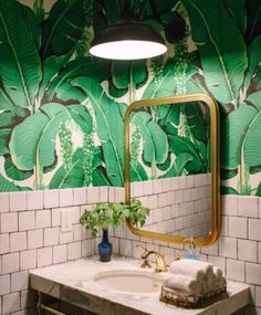 White tiles with big green leaves on the wall. The mirror is an important detail, its golden frame breaks with those two powerful textures.