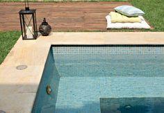 A borda da piscina de placas de quartzito é parcialmente abraçada pelo deque de cruzetas. Repare na disposição do banco dentro da piscina, que tem pastilhas cerâmicas da Jatobá nos tons de azul viscaya, ibérico e índico