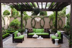 Just lovely, great little beds with roses and boxwoods and the plants trained to create the circular pattern dresses up the fence beautifully- Green & brown outdoor deck patio design with dark brown stained furniture.  #backyardfantasy #outdoorliving #balcony
