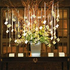 """Brides: Modern Hanging Escort-Card Tree Display. Instead of a standard table, the couple had an escort-card """"tree."""" Cards by designer Melissa Knapp were tied to ribbons that were then attached to the branches. """"The display added a fun visual element to the room,"""" Jessica says. All flowers by William Mizuta Private Florist."""