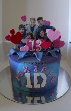 One Direction themed cake for a sweet 13th birthday! Created by Shandi Sansom from Sugar Kissed.This cake is a bubble gum swirl cake. Topped with upright 1D boys and heats. Perfect for any girl! Visit my Facebook page: www.facebook.com/sugarkissedshandi