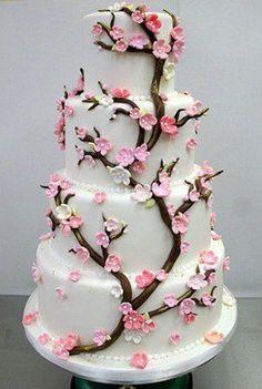 Pastel con árbol de azúcar y flores rosadas.
