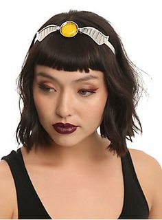 """No need to chase after the Golden Snitch, it's attached to this silver tone headband from <i>Harry Potter</i>. Design features burnished silver tone wings with a large faceted golden yellow gem detail. 150 points go to you!<br><ul><li style=""""list-style-position: inside !important; list-style-type: disc !important"""">Alloy</li><li style=""""list-style-position: inside !important; list-style-type: disc !important"""">Imported<br></li></ul>"""