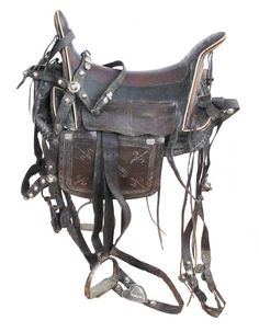 A CIRCASSIAN SADDLE AND TRAPPINGS The wooden tree covered in panels of black and light brown leather, the pommel, cantle and rails with elegant inlaid bone borders and curvilineal decorative elements, the saddle aprons and skirts tooled in traditional motifs. Silvered and enameled stirrups. Mid-19th century.