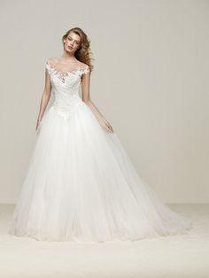 Drosel ist ein romantisches Brautkleid im Prinzessin-Stil. Voluminöser, tief angesetzter Rock aus Tülllagen. Off-Shoulder-Ausschnitt aus hauchzartem Tüll. Pronovias