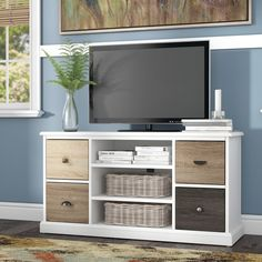 Add an airy, understated touch to any ensemble with this lovely TV stand, pairing a crisp white-finished frame with earthy brown cabinet fronts. Set it against a light blue wall in the living room to lean into a neutral, earthy palette in your space, then round out the ensemble with a beige, red, and green geometric rug and minimalist abstract print above. Featuring three open shelves and four cabinets, this design offers effortless storage in any ensemble. Use the open shelving to keep…
