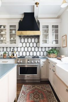 A black enameled range hood with a brass trim is fixed to white and black geometric backsplash tiles beneath glass front cabinets and above a stainless steel oven range.