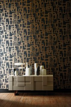 A retro graphic wallpaper design with the effect of hand painted brushstrokes in gold and dark grey.