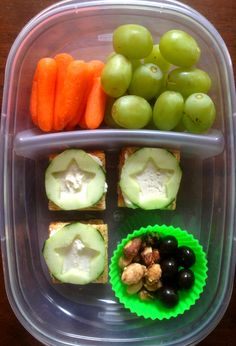 Easy kid bento lunchbox ideas: Triscuits with cream cheese and cucumber, cranberry-glazed almonds, chocolate covered blueberries, carrots, grapes