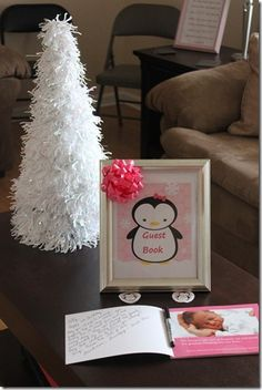 """Love this idea. For our guestbook, I made a Shutterfly book that has pictures from each month of her first year… there is a blank page for each page of pictures so that our guests could leave a special message… we joked around that we will show her this on her 21st birthday"""""""
