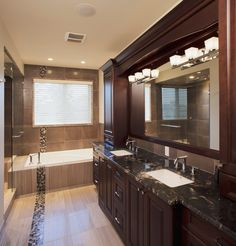 Titanium Gold schist bathroom countertop with dark cherry cabinets and modern tile flooring.