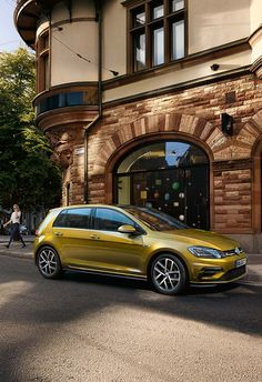 The Volkswagen Golf photographed driving through the old part of town past beautiful vintage architecture.