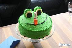A standard round cake tin cake 2 cupcakes as the eyes. Then melted white chocolate, dribbled on baking paper in a large circle shape, stuck half an oreo cookie onto that,waited for it to set and voila, frogs eyes done! mouth just a strip of black licorice and the tongue a rasberry sour strip, then some green pebbles for added decoration around the edge and as eyebrows and you are done!