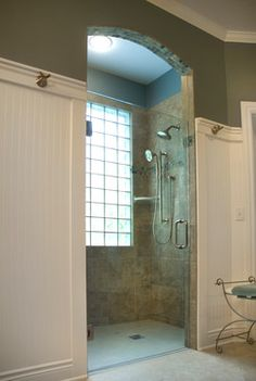 This shower includes a no threshold approach and an arched entry. Glass shower door lets light in from the glass block window and upgraded shower heads finish off this tiled shower.