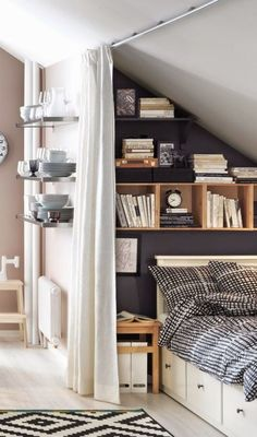If you don't have a dedicated guest bedroom, that doesn't mean your overnight guests have to sleep on the sofa. A daybed hidden in a tiny nook in your attic (with a curtain door!) offers a sweet escape for visitors. Click through for more on this and other ideas for how to upgrade your attic and unfinished attic storage solutions.