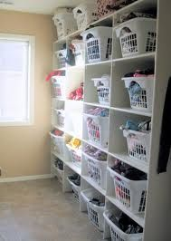 Large shelves perfectly-sized (DIY?) for the many (20+) white uniform large plastic laundry baskets... Great for organizing the laundry room of a large family.  This would be so cute (but a lot more expensive) with wicker laundry baskets that aren't see through.