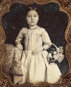 Portrait of little girl leaning on a table carrying a basket of flowers. notice she is wearing stays in the dress or a corset.