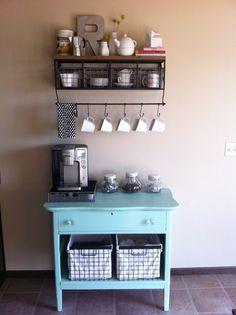 Outra ideia bacana, reaproveitamento de cômoda renovada com pintura azul e 2 cestas. Na parede suporte para xícaras e prateleira ☕