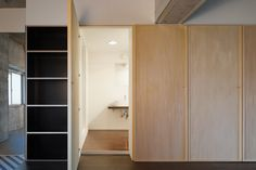 Wooden doors open to reveal bathroom and kitchen facilities in this apartment in Tokyo