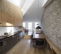 This mews house in Dublin, designed by Irish studio DUA for a young bachelor, features a sunken concrete bathtub, and reclaimed-brick and pine-plywood walls