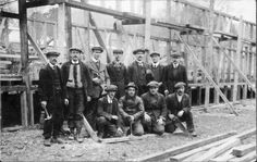 Workmen pause for a group photograph during the construction of a guard room for an army camp in the Winchester area.  The postcard, which was sent to an address in Bradford, Yorkshire, is postmarked 2.2.1915