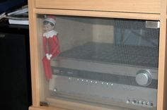 """Elf on the Shelf 2010 (Fizzy): 12.04: Usually Max our cat is snoozing here in the """"heat box"""" on top of the tuner. He climbs into the entertainment center from the back and spends most of his day there. I may try to get another photo of Fizzy with Max in there.   Photo by G."""